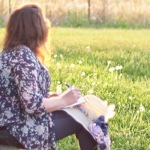 woman looking over a green field while writing