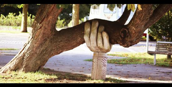 a carved wooden hand coming out of the ground is holding up the trunk of a tree