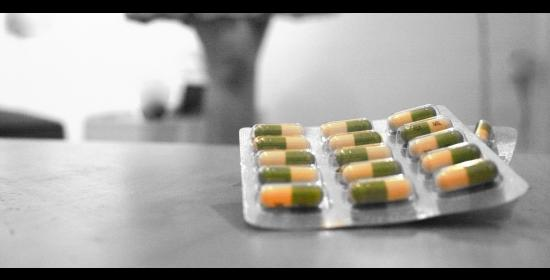 packet of prozac pills sitting on a counter with a figure in the background