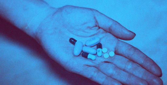 blue picture of a hand holding pills