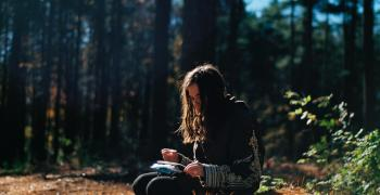 woman writing in journal over the woods